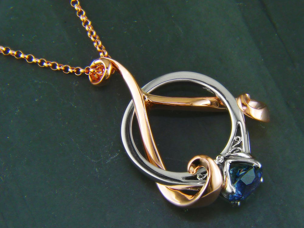Custom made rose gold vine pendant with a custom platinum and sapphire mounting, representing an upside down heart with a drying flower in the middle.