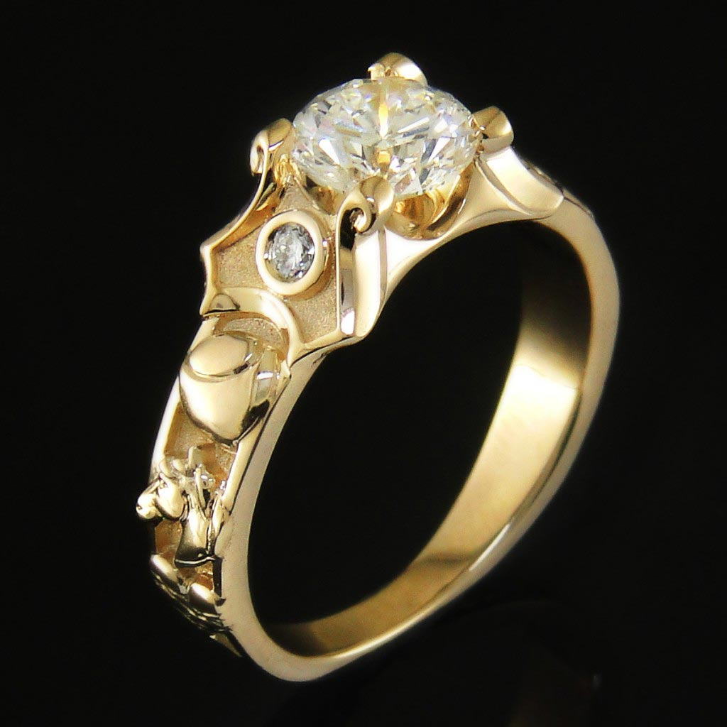 Custom cast 14k gold mounting with a round brilliant cut center diamond. Both sides of the ring are adorned with small icons symbolizing different stages in the couple's time together.