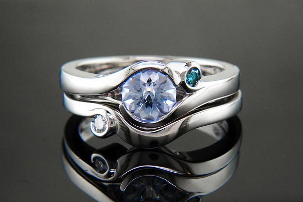 Platinum wrap-style engagement ring with a custom water lily-cut sapphire center, blue diamond accent and matching diamond shadow band