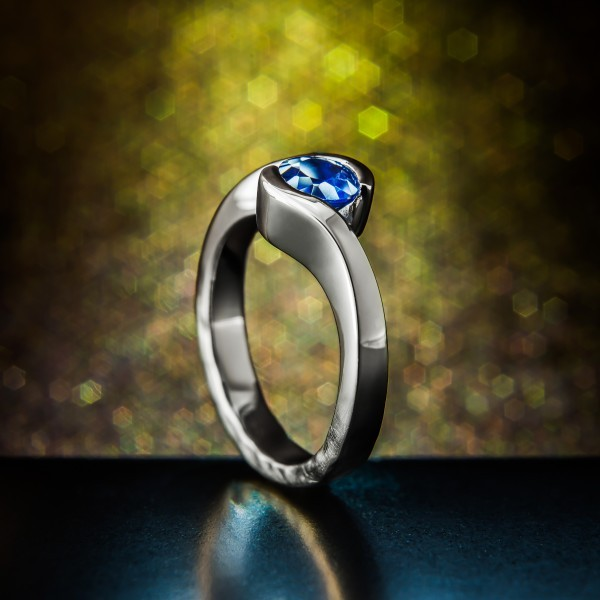 This sapphire wrap ring is unique in that the smooth bumps along the base of the ring to signify the walls of a glacial tunnel were formed into the model of which the ring was cast, rather than simply hammered in at the end. This approach achieved not just the look the client was after, but also ensures it will stay that way through  the ages.