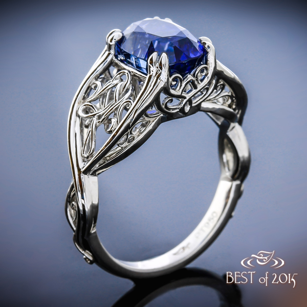 Custom made platinum ring with dazzling cushion-cut sapphire center and hand fabricated filigree accents.