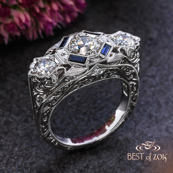 Antique inspired diamond ring in platinum with baguette-cut sapphires and engraved motifs as a halo.