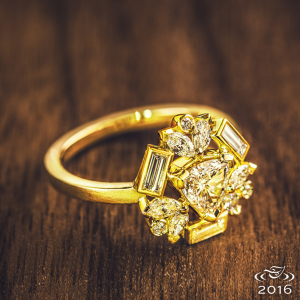 A kaleidoscope of baguette and round melee diamonds are held in delicate bezels around a trillion diamond center. A matte finish highlights the warm golden tones of Fairmined Gold.