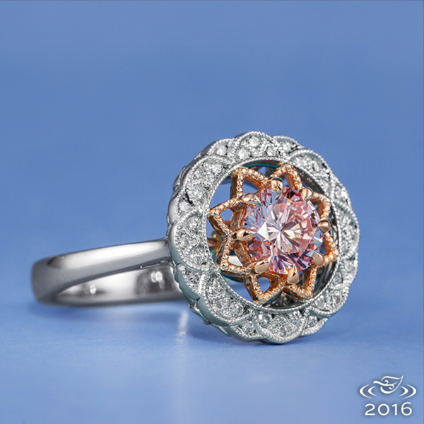 At the center of this delicate engagement ring is a pink diamond with stunning color highlighted by delicate rose gold. Platinum scallops set with diamond melee encircle the edge of the halo and are met by an airy under gallery of delicate curls.