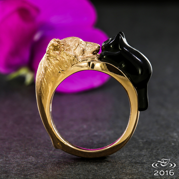Inspired by a couple's pets, this ring features their cat hand carved of onyx nose to nose with their dog, hand carved and cast in rose gold.