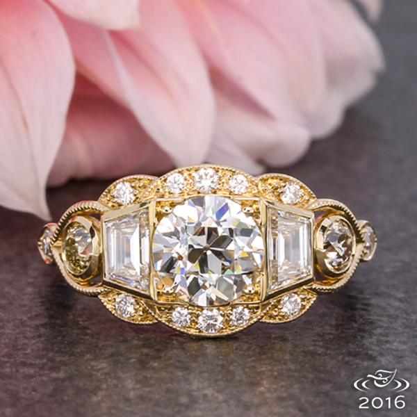 An old European cut diamond is framed by two trapezoid diamonds and a yellow gold scalloped Art Deco halo.