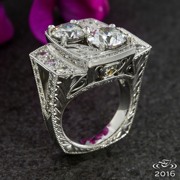 Two diamonds, 1ct and 1.71 ct, are the centerpiece of this intricate anniversary ring highlighted by a halo of diamonds and milgrain. Filigree and half wheat engraving add vintage touches to this platinum piece.