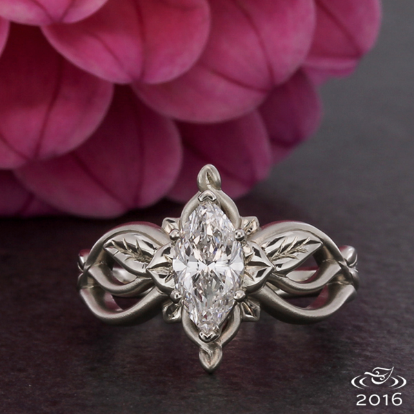 White gold in polished and matte finishes flows to create an organic mounting for a marquise diamond accented by hand engraved leaves.