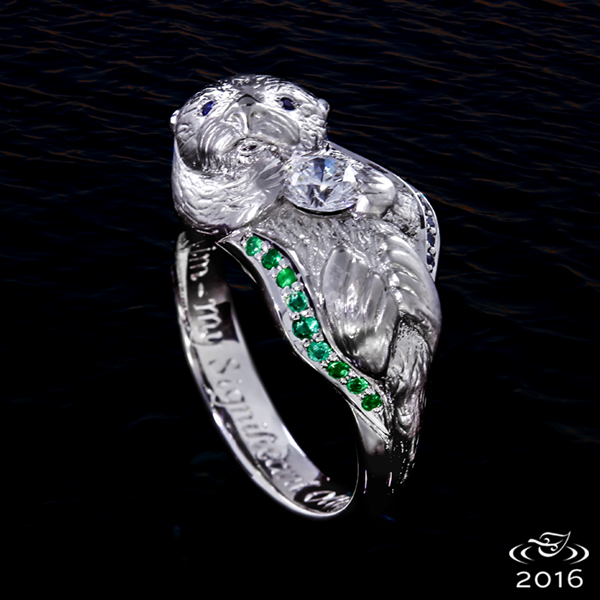 A realistic platinum otter ring holds a diamond in its paws while bead set sapphire and emerald waves wrap around its body.
