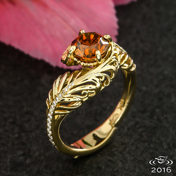 Two golden feather plumes dotted with diamonds and embellished with filigree intertwine to hold a natural orange diamond.