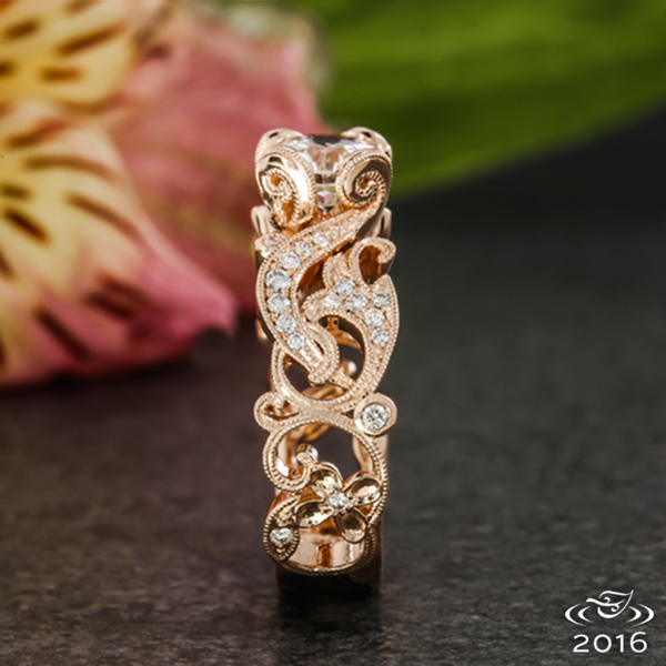 Bead set diamonds fill every pierced scroll, leaf and swirl and gently curl to hold a round brilliant diamond in this delicate engagement ring.
